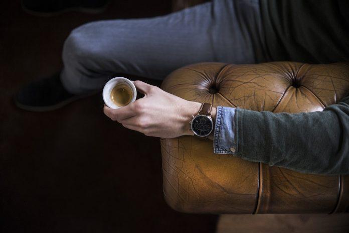 muž sediaci na pohovke chesterfield s kávou v ruke