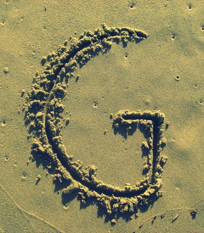 písmeno G napísané v piesku