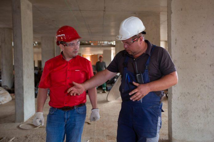 dvaja muži s prilbami na stavbe