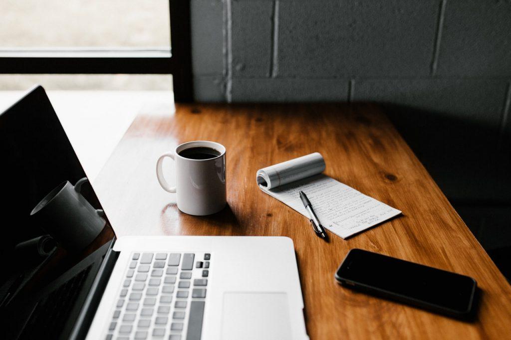 počítač a zápisník na jednoduché hľadanie nehnuteľnosti