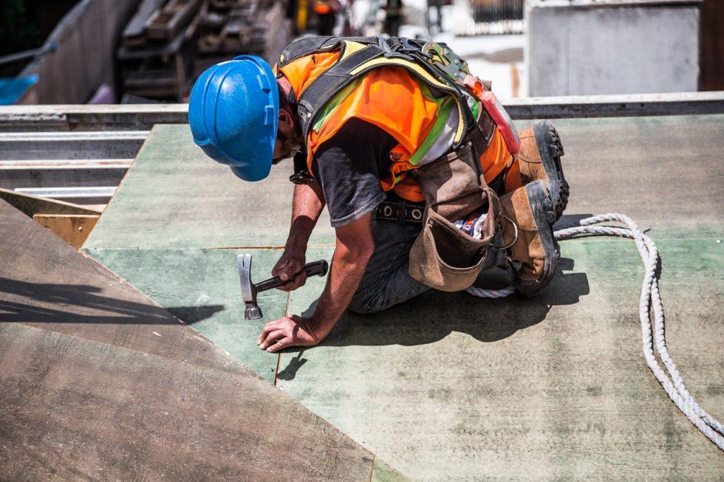 stavbár pracujúci na správnej montáži tepelnej izolácie strechy