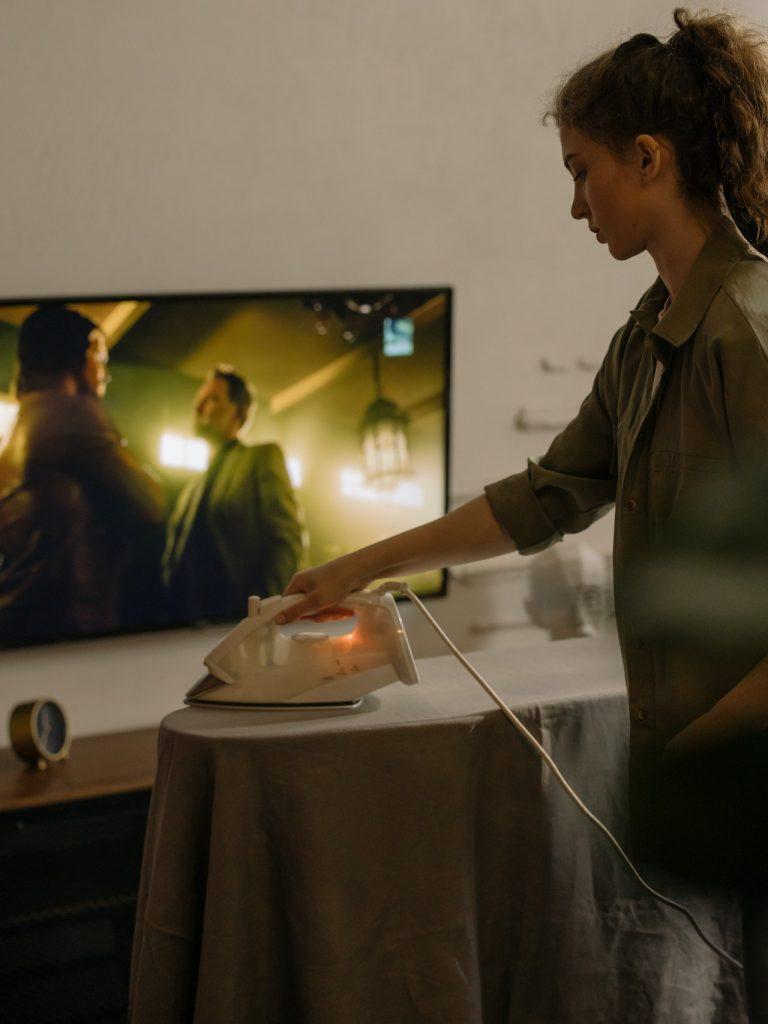 mladá žena žehlí obľúbenú košeľu