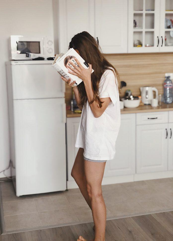 mladá žena čítajúca knihu stojaca pred chladničkou