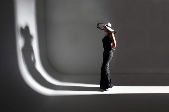 žena v čiernom obdivujúca svoj tieň