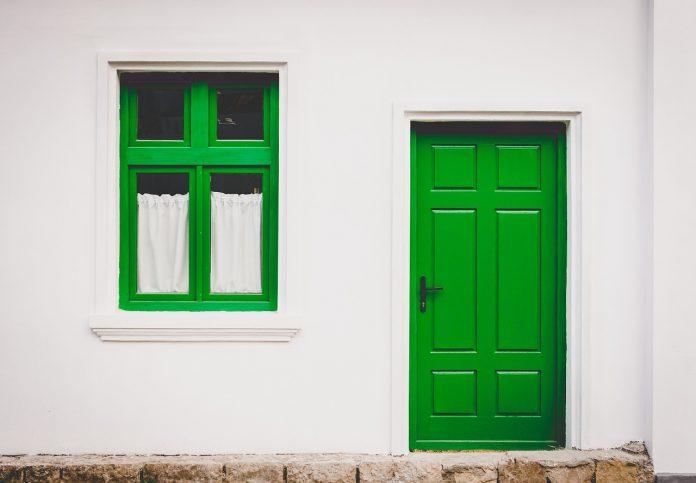 čerstvo vymaľovaná fasáda domu so zelenými dverami a oknom