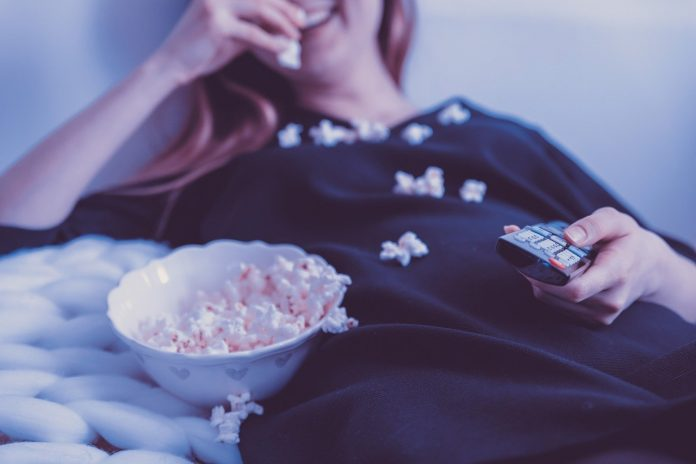mladá žena sleduje dokumentárny seriál IKONY s popcornom