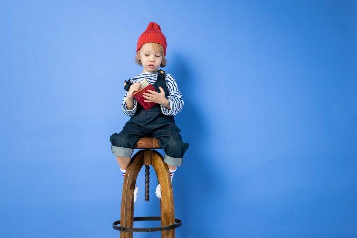 malé dieťatko sediace na pohodlnej barovej stoličke z dreva