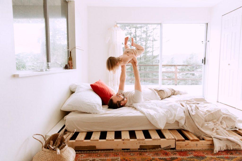 otec s dcérou ležia v čistých perinách na posteli z paliet