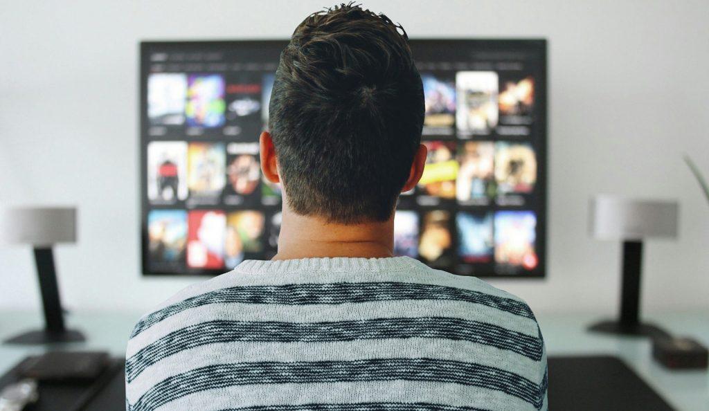 mladý muž sediaci pred televíznou obrazovkou a sledujúci seriál ABSTRACT na Netflixe