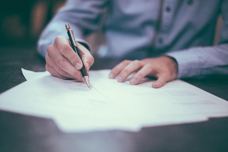mladý muž podpisuje darovaciu zmluvu v modernej kancelárií
