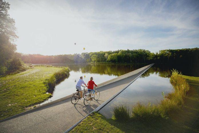 mladý manželský pár na cyklomoste - jednom z najobľúbenejších turistických atrakcií v Belgicku