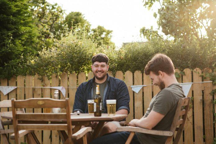 dvaja mladí muži sediaci na terase pri fľaši s pivom