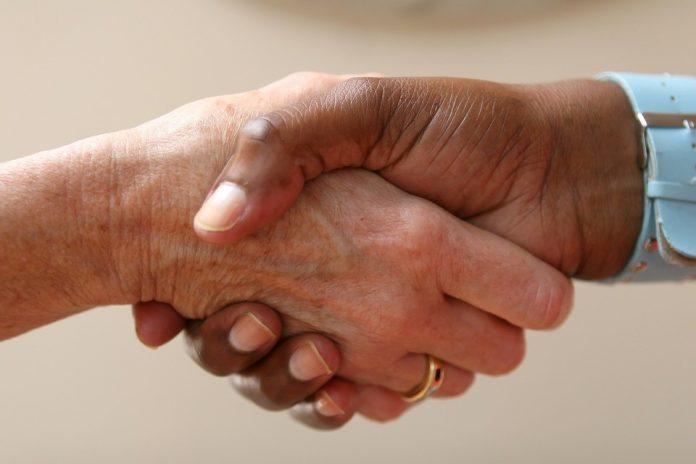 muž so ženou si podávajú ruky pri podpise darovacej zmluvy