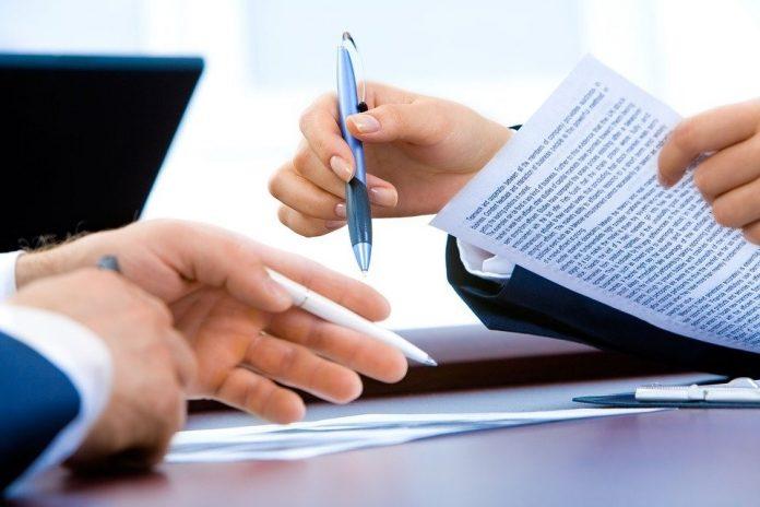mladý muž podpisuje darovaciu zmluvu v modernej kancelárii