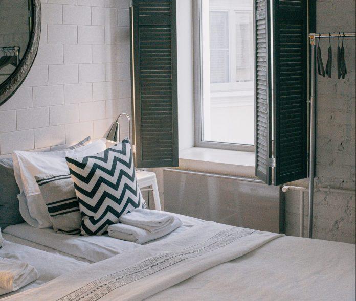 Posteľ pri okne čiernobiele dekorácie v spálni