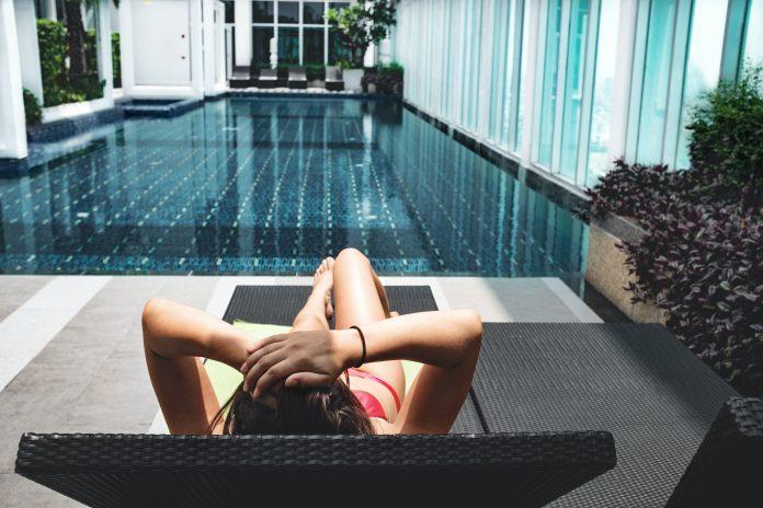 Žena ležiaca na lehátku pri bazéne