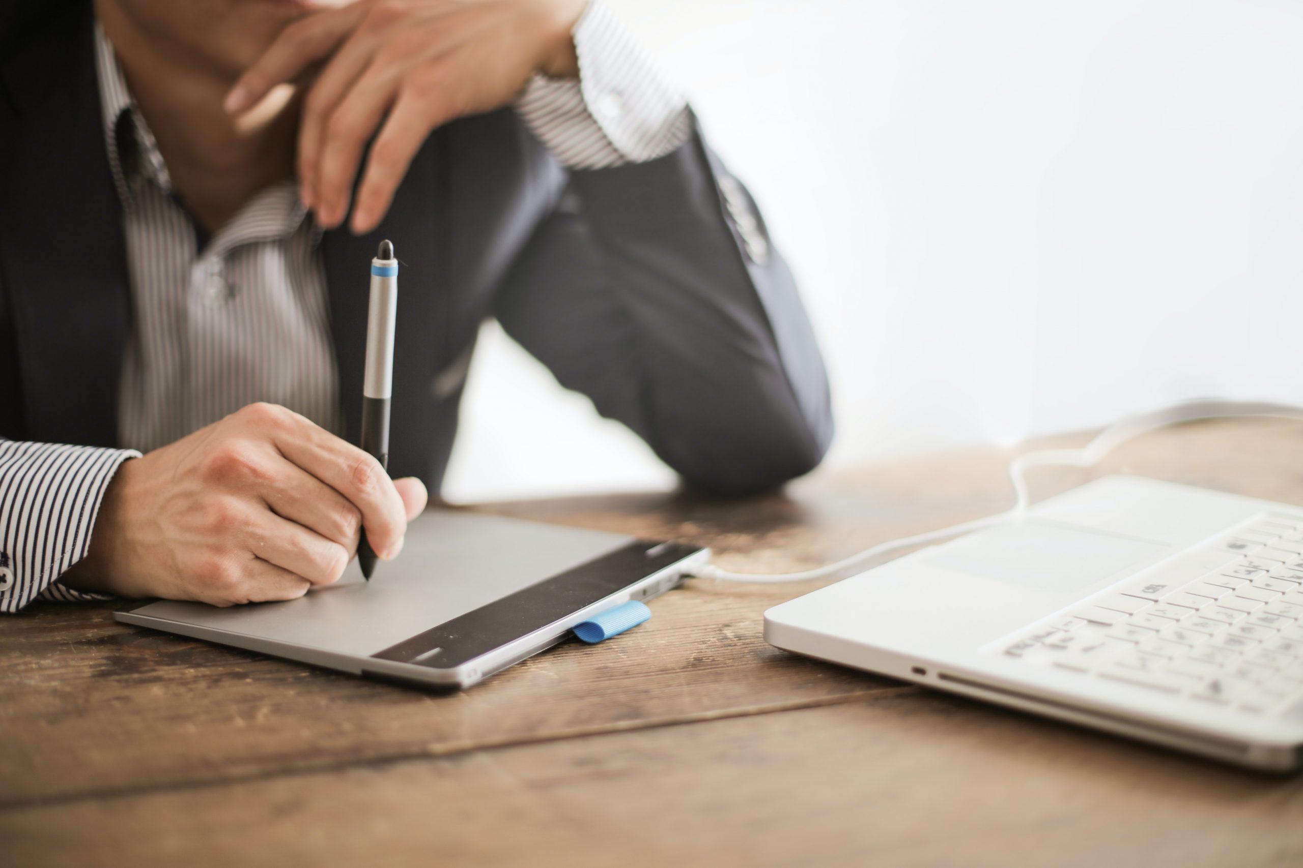 Muž sediaci za stolom s notebookom a perom