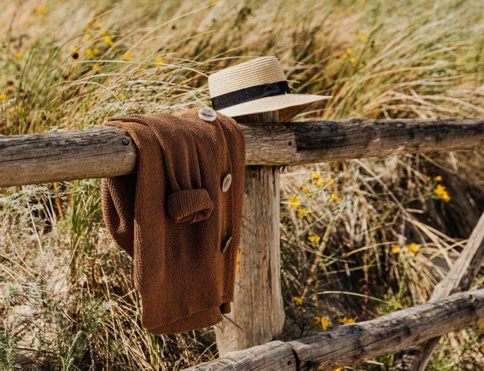 Klobúk a sveter prevesený cez drevený plot