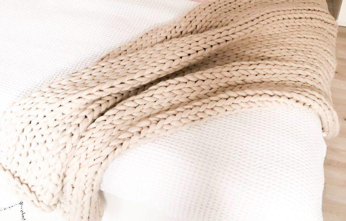 Posteľ s prehodenou bežovou dekou