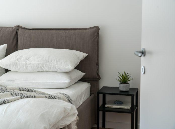 Spálňa sivá posteľ biele vankúše malý nočný stolík