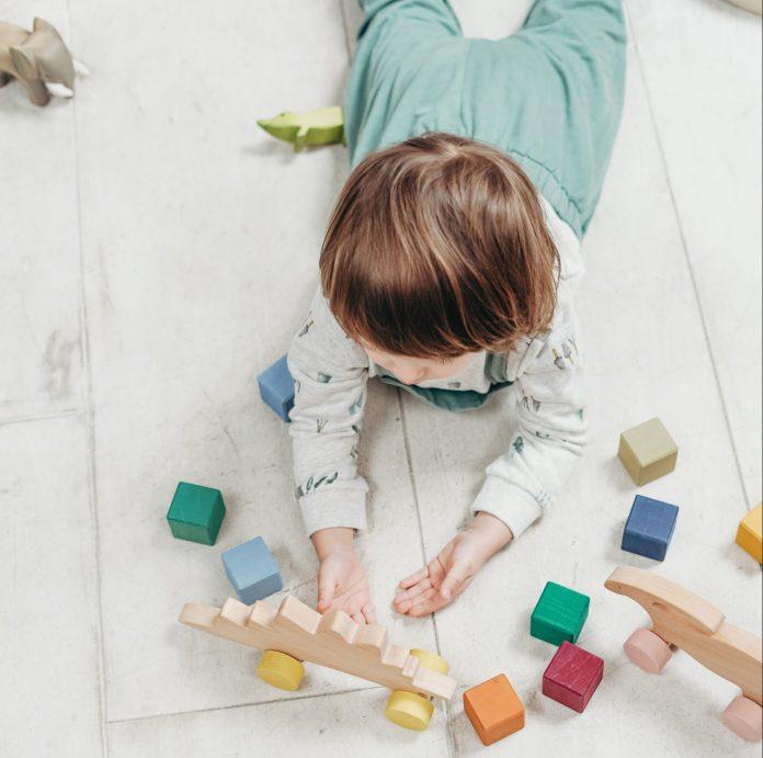 Ležiace dieťa na zemi drevené hračky