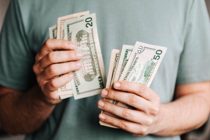 človek držiaci bankovky Peniaze