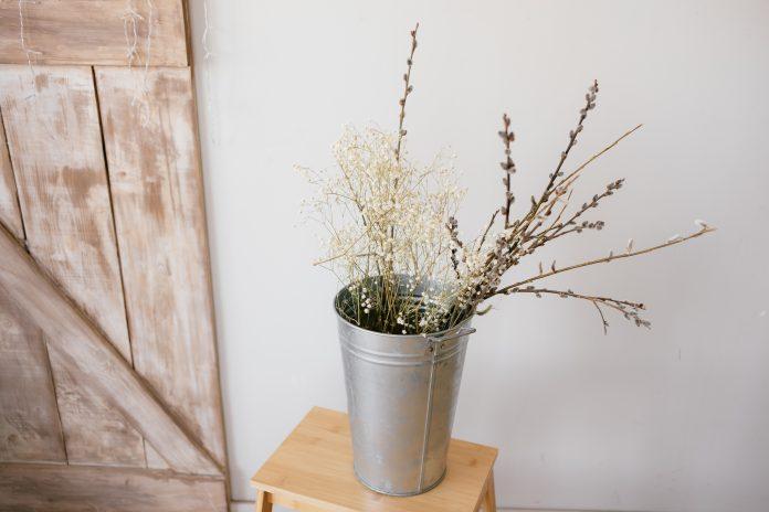 Váza s konárikmi a drevené dvere s patinou