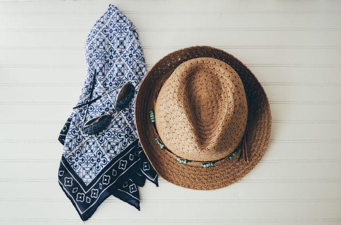 klobúk a šatka zavesené na stene