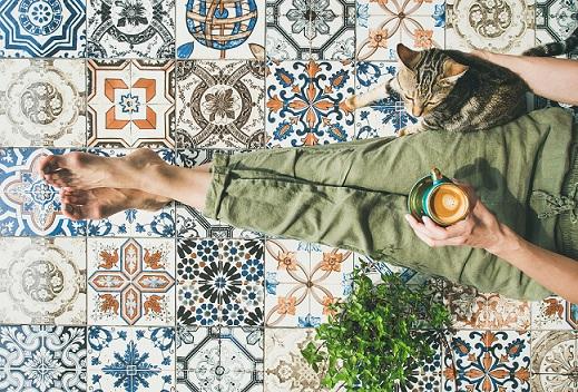 žena s mačkou a kávou sediaca na vzorovanej dlažbe